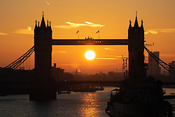 © Licensed to London News Pictures. 21/10/2018. London, UK. The sun rises through the middle of Tower Bridge this morning, as temperatures are set to reach highs of 18 degrees Celsius in the capital later today. Photo credit : Tom Nicholson/LNP