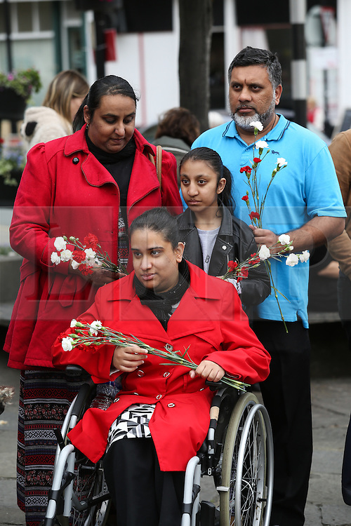 © Licensed to London News Pictures. 15/07/2016. Batley, UK. A family holds flowers as she waits for Jo Cox's funeral cortege to pass through her hometown of Batley, West Yorkshire. The Labour MP was stabbed and shot in the street as she left her constituency surgery last month. Thomas Mair was arrested in connection with the murder and is set to face trial this year.  Photo credit : Ian Hinchliffe/LNP