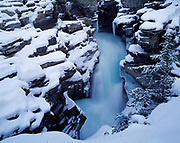 Winter view of the Athabasca River spilling over Athabasca Falls, Jasper National Park, Alberta, Canada.