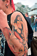 A young female punk with a big tattoo of a sexy nude woman on her arm and hand