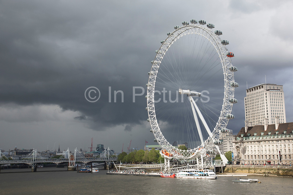 London Eye contrasts against a steel sky, London, UK. The London Eye is a giant Ferris wheel on the South Bank of the River Thames in London. Also known as the Millennium Wheel, its official name was originally the British Airways London Eye, then the Merlin Entertainments London Eye, and since January 2011, the EDF Energy London Eye.