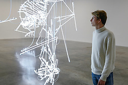 """© Licensed to London News Pictures. 06/02/2020. LONDON, UK. A staff member views """"... take Apprentice in the Sun III, 2020, by Cerith Wyn Evans. Preview of """"No realm of thought... No field of vision"""" by Cerith Wyn Evans at the White Cube gallery in Bermondsey.  The exhibition runs 7 February to 19 April 2020.  The show comprises installations, sculpture and painting.  Photo credit: Stephen Chung/LNP"""
