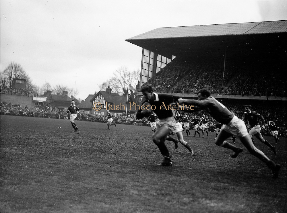 Scottish back R C Cowen. on the left, in possession, hands off W R Hunter, Irish back,..Irish Rugby Football Union, Ireland v Scotland, Five Nations, Landsdowne Road, Dublin, Ireland, Saturday 24th February, 1962,.24.2.1962, 2.24.1962,..Referee- N M Parkes, Rugby Football Union, ..Score- Ireland 6 - 20 Scotland, ..Irish Team, ..F G Gilpin, Wearing number 15 Irish jersey, Full Back, Queens University Rugby Football Club, Belfast, Northern Ireland,..W R Hunter, Wearing number 14 Irish jersey, Right Wing, C I Y M S Rugby Football Club, Belfast, Northern Ireland, ..M K Flynn, Wearing number 13 Irish jersey, Right Centre, Wanderers Rugby Football Club, Dublin, Ireland, ..D Hewitt, Wearing number 12 Irish jersey, Left centre, Instonians Rugby Football Club, Belfast, Northern Ireland,..N H Brophy, Wearing number 11 Irish jersey, Left wing, Blackrock College Rugby Football Club, Dublin, Ireland, ..G G Hardy, Wearing  Number 10 Irish jersey, Stand Off, Bective Rangers Rugby Football Club, Dublin, Ireland,  ..J T M Quirke, Wearing number 9 Irish jersey, Scrum Centre, Blackrock College Rugby Football Club, Dublin, Ireland, ..S Millar, Wearing number 1 Irish jersey, Forward, Ballymena Rugby Football Club, Antrim, Northern Ireland,..A R Dawson, Wearing number 2 Irish jersey, Forward, Wanderers Rugby Football Club, Dublin, Ireland, ..R J McLoughlin, Wearing number 3 Irish jersey, Forward, University College Dublin Rugby Football Club, Dublin, Ireland, ..W A Mulcahy, Wearing number 4 Irish jersey, Captain of the Irish team, Forward, Bohemians Rugby Football Club, Limerick, Ireland,..W J McBride, Wearing number 5 Irish jersey, Forward, Ballymena Rugby Football Club, Antrim, Northern Ireland,..D Scott, Wearing number 6 Irish jersey, Forward, Malone Rugby Football Club, Belfast, Northern Ireland, ..M L Hipwell, Wearing number 8 Irish jersey, Forward, Terenure Rugby Football Club, Dublin, Ireland, ..M G Culliton, Wearing number 7 Irish jersey, Forward, Wanderers Rugby Football Club, D