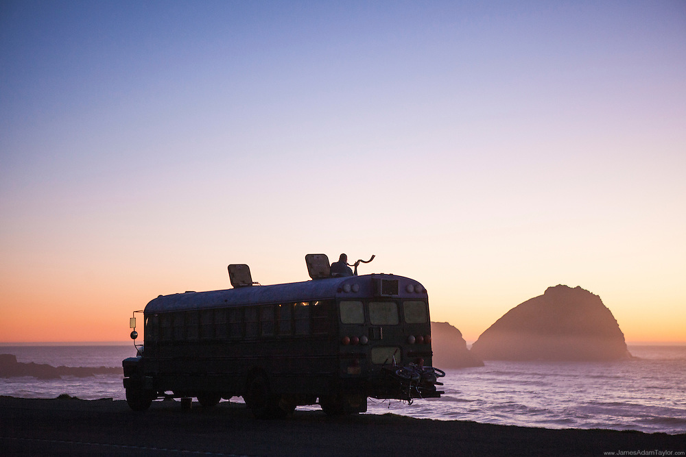 Sunset over the Pacific Ocean, the sihloette of a bohemian bus with a man standing in the roof hatch blowing a shofar (animal horn trumpet).  Highway 101, Del Norte County, CA.