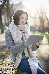 Mature woman using digital tablet in the park and smiling, Bavaria, Germany