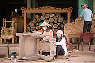 Vietnameses women working on a chair in the craft village of Dong Ky, specialized in wood furnitures manufacture. Vietnam, Asia