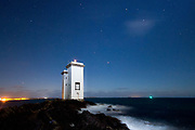 A torch lit long exposure of Port Ellen lighthouse at night