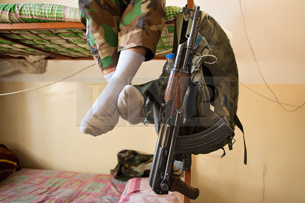 © Licensed to London News Pictures. 29/06/2014. Khanaqin, UK Khanaqin, Iraq. A Kurdish peshmerga fighter, with his rifle hanging on his bunk bed, relaxes at a peshmerga base in Khanaqin, Iraq. Counted by Kurds as part of their homeland, fighting in the town of Jalawla now consists of occasional skirmishes and exchanges of fire between snipers and heavy machine guns on both sides.<br /> <br /> The peshmerga, roughly translated as those who fight, is at present engaged in fighting ISIS all along the borders of the relatively safe semi-automatous province of Iraqi-Kurdistan. Though a well organised and experienced fighting force they are currently facing ISIS insurgents armed with superior armament taken from the Iraqi Army after they retreated on several fronts. Photo credit : Matt Cetti-Roberts/LNP