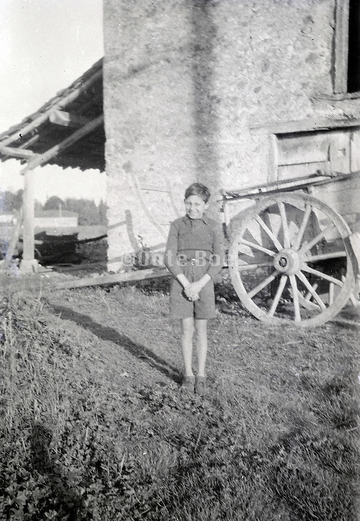 young boy in front of barn part of the farm countryside 1950s Europe