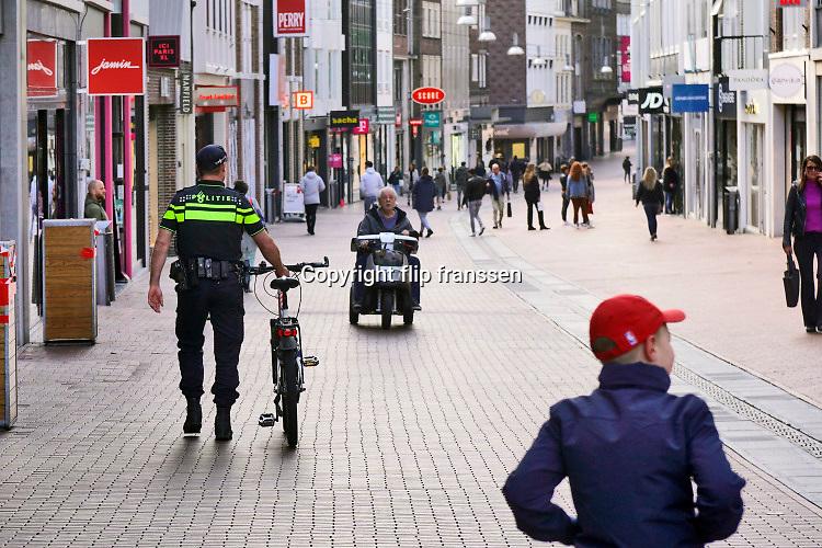 Nederland, Nijmegen, 30-4-2020  Een politieagent looppt met zijn fiets aan de hand door een winkelstraat in het centrum van de stad . De politie houdt extrat toezicht en doet handhaving van de coronamaatregelen zoals de anderhalve meter afstand die buiten gehouden moet worden .Foto: Flip Franssen