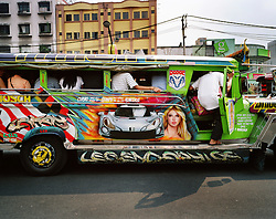 """A """"Jeepney"""" adorned with a painting of Britney Spears, drives through the crowded streets of Manila, Philippines on Dec.  2006. Many OFWs buy Jeepneys, flamboyantly decorated U.S. military jeeps left over from World War II, with their money earned abroad as a way to earn a living at home."""