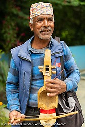 Roadside musician playing a traditional Nepalese Sarangi on Motorcycle Sherpa's Ride to the Heavens motorcycle adventure in the Himalayas of Nepal. Riding from Pokhara to the National Park in Chitwan, Monday, November 11, 2019. Photography ©2019 Michael Lichter.