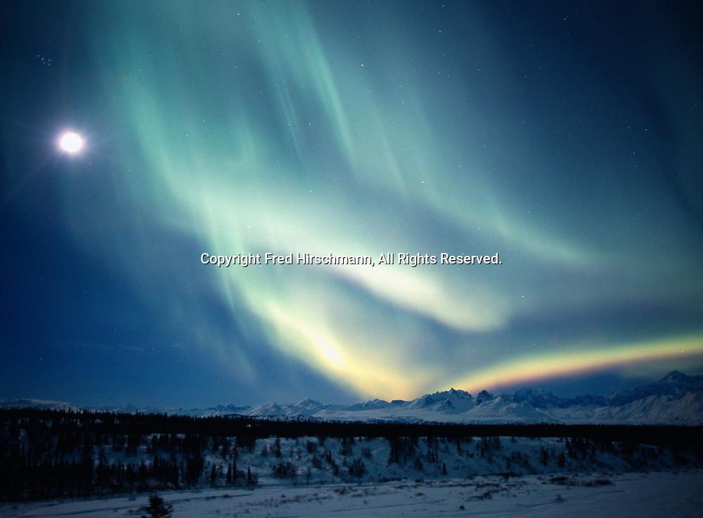 Green aurora and moon above the Chulitna river and Alaska range, geomagnetic storm on January 19, 2005, Denali State Park and Denali National Park, Alaska.