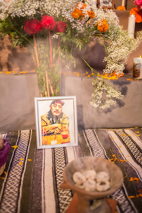 New York, NY, October 31, 2013. A memorial to a man includes his framed portrait in front of a vase of flowers including orange marigolds. In the foreground is a censor burning copal, sometimes called Mexican frankincense.