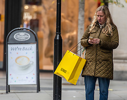 © Licensed to London News Pictures. 26/11/2020. London, UK. A shopper in Oxford Street, London as Health Secretary Matt Hancock reveals his plans today for a new Covid 3 tiered system of restrictions. As expected, London escape the highest restriction of Tier 3 and will be in Tier 2 with the possibility of shops, pubs and restaurants to open up again for the Christmas period. Photo credit: Alex Lentati/LNP