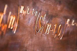 Mathematical symbols cut into a band of copper running through the Winton Beauty of Mathematics Garden, Chelsea Flower Show 2016. Used as backing to seat and staircase bannister