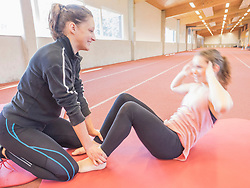 Fitness instructor helping young woman doing sit-ups in athletics hall on tartan track, Offenburg, Baden-Wuerttemberg, Germany