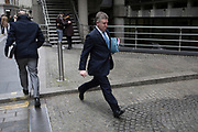A businessman clutching files under one arm strides past Lloyds of London on Lime Street in the City of London, the capital's financial district, 7th March 2018, in London England.