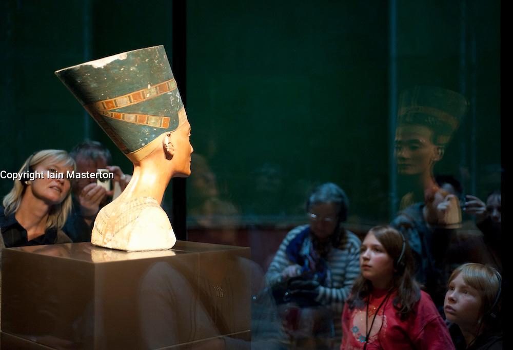 Visitors looking at bust of Nefertiti at Neues Museum Berlin