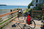 My road touring bicycle rests on a deck of Robert L. Smith Park (locally called Boy and Dog Park for its 1986 sculpture) with a view across Saratoga Passage to the Cascades Range. This public stairway descends to scenic Seawall Park, in the village of Langley, Whidbey Island, Washington, USA.