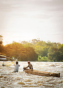 Two fishermen with boat and fishing net in the San Juan river, El Castillo, Rio San Juan Department, Nicaragua