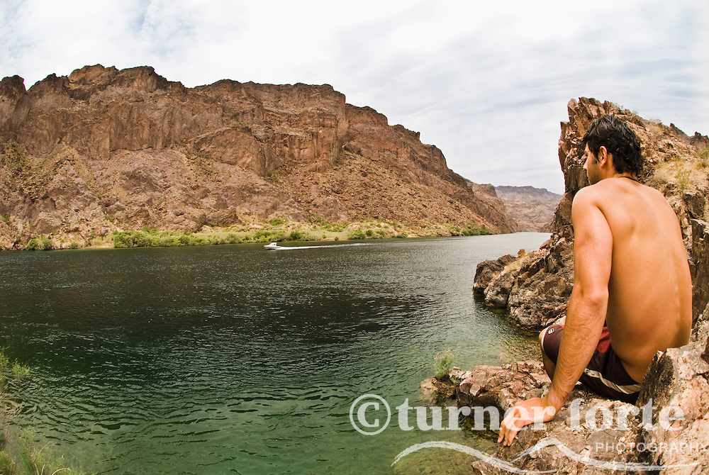 A man watches a boat head down the Colorado River, The Black Canyon, Nevada.