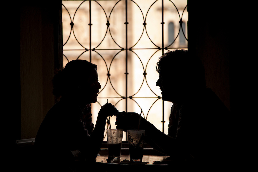 North America, Mexico, Oaxaca Province, Oaxaca,  young couple enjoying iced coffees in cafe with wrought-iron window grill, silhoutette