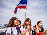 """27 NOVEMBER 2012 - BANGKOK, THAILAND:  School girls pray at Wat Saket during the temple's annual fair. Wat Saket, popularly known as the Golden Mount or """"Phu Khao Thong,"""" is one of the most popular and oldest Buddhist temples in Bangkok. It dates to the Ayutthaya period (roughly 1350-1767 AD) and was renovated extensively when the Siamese fled Ayutthaya and established their new capitol in Bangkok. The temple holds an annual fair in November, the week of the full moon. It's one of the most popular temple fairs in Bangkok. The fair draws people from across Bangkok and spills out in the streets around the temple.   PHOTO BY JACK KURTZ"""