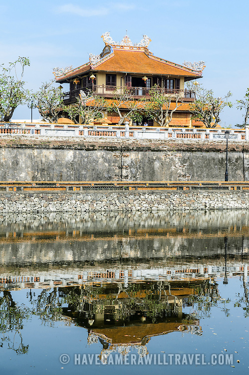 A building at the Imperial City in Hue, Vietnam, is reflected on the water of the defensive moat. A self-enclosed and fortified palace, the complex includes the Purple Forbidden City, which was the inner sanctum of the imperial household, as well as temples, courtyards, gardens, and other buildings. Much of the Imperial City was damaged or destroyed during the Vietnam War. It is now designated as a UNESCO World Heritage site.