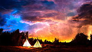 Panorama of a colorful stormy sky during a sunset with lightening and two Kiowa teepees lit from the fires inside them.