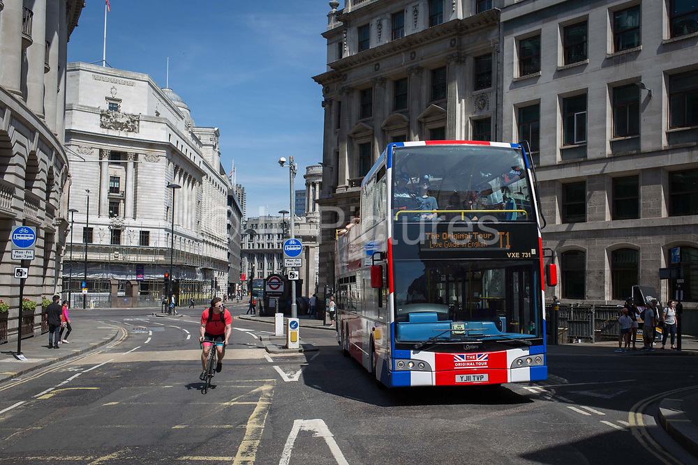 A cyclist overtakes a tour bus with The Original Tour latest branding of a Union jack flag drives along King William Street, on 7th July 2017, in the City of London.
