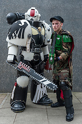 © Licensed to London News Pictures. 24/05/2015. London, UK. Men dressed as (L to R) Space Marine and Imperial Guard from Warhammer pose, as fans of anime, comic books, video games and more gather in large numbers at the Excel Centre to attend the bi-annual MCM Comic Con. Photo credit : Stephen Chung/LNP