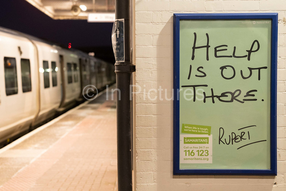 A train is stopped at Loughborough Junction railway station where a Samaritans poster urges those with mental health issues, or even thoughts of suicide, to seek help from the registered charity aimed at providing emotional support to anyone in emotional distress, struggling to cope, or at risk of suicide throughout the United Kingdom and Ireland, often through their telephone helpline, on 26th February 2021, in London, England.