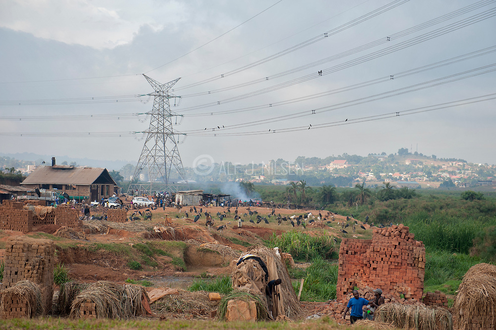 Building houses of bricks along the main street in Kampala, Uganda. In the back ground hundreds of Marabou storks gather to feed on human waste while large power masts and cables penetrates the area.