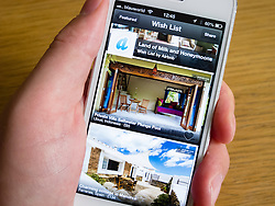 Using Airbnb app to book holiday accomodation on a white iPhone 5 smartphone