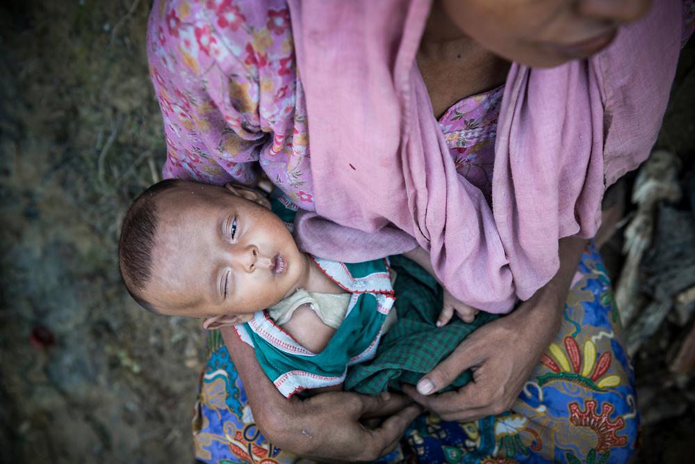 A Rohingya mother holds her two-month-old daughter outside their shelter at Jamtoli refugee camp near Cox's Bazar, Bangladesh
