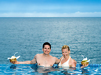 beautiful caucasian couple enjoying their vacation in a beautiful swimming pool by the seaside