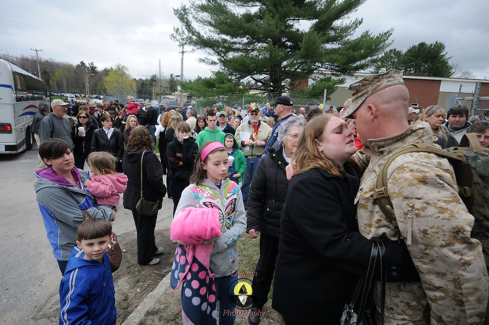 5/5/11 -- TOPSHAM, Maine.  U.S. Marine Lance Cpl John Crowley, right, of Bath kisses his wife, Kristin goodbye just before getting on the bus and heading for deployment. Marine Reservists departed from Topsham on Thursday for the start of a year-long deployment to Afghanistan amidst a crowd of family, friends and well-wishers. This mission will be different from others, said several Marines, because instead of doing combat operations they will be teaching the Afghan National Army to operate independently. They travel first to California for several months of training and are planning to return in May 2012. Photo by Roger S. Duncan.