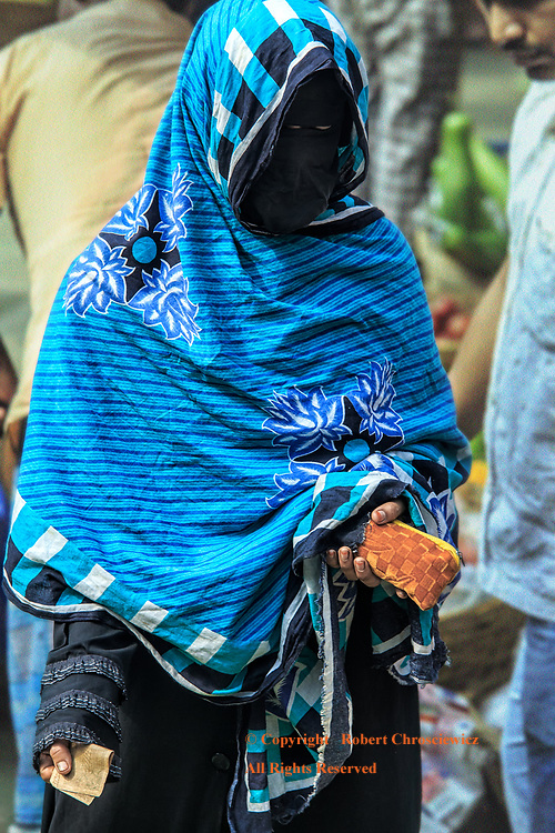 Fashion of Oppression: This woman shops the morning market wearing her burka, the fashion of her oppression; both condoned and promoted by her social and religious standing, Dhaka Bangladesh.