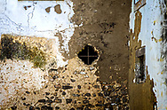 An image of an old ruin of a castle in Tavira, Portugal, wilh a small window with a crossbar.