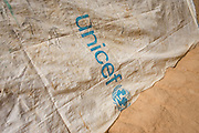 UNICEF-supplied sheeting used to cover a makeshift roof lining of a home in the 4 sq km Abu Shouk refugee camp which is (disputedly) home to 38,000 displaced persons and families on the outskirts of the front-line town of Al Fasher (also spelled, Al-Fashir) in north Darfur. .