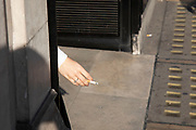A womans hand appears to flick the ash as she smokes a cigarette in London, United Kingdom. Smoking is a global public health issue as advice says that giving up is the single best thing you can do to prevent hearth disease.