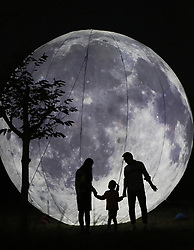 October 3, 2017 - A family pose for pictures near a giant moon-like lantern in Zouping County, east China's Shandong Province, Oct. 3, 2017. Various activities are held around China during the National Day holiday. This year it has been extended by one more day as the Mid-Autumn Festival falls on Oct. 4.  (Credit Image: © Dong Naide/Xinhua via ZUMA Wire)