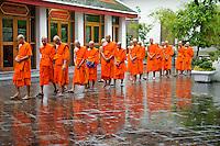 Buddhist monks walk in the rain at temple Wat Pho, Bangkok, Thailand.