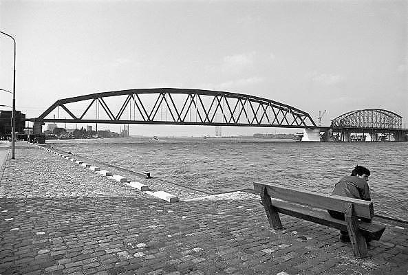Nederland, Nijmegen, 1-10-1983Enkele maanden na de vervanging van de oude spoorbrug, die uit drie aparte bogen bestond, door een enkelvoudige overspanning van 235 meter, dan de grootste van ons land. Het noordelijke brugdeel is in september 1983 vervangen door een betonnen aanloopbrug. Op de foto is dat net gebeurd en wordt het laatste deel van de oude brug ter plekke gesloopt. De nieuwe brug is in 2004 uitgebreid met een fietsbaan, de zgn. snelbinder.