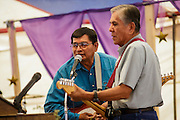 """12 JULY 2012 - FT DEFIANCE, AZ: Musicians perform worship music at the 23rd annual Navajo Nation Camp Meeting in Ft. Defiance, north of Window Rock, AZ, on the Navajo reservation. Preachers from across the Navajo Nation, and the western US, come to Navajo Nation Camp Meeting to preach an evangelical form of Christianity. Evangelical Christians make up a growing part of the reservation - there are now more than a hundred camp meetings and tent revivals on the reservation every year. The camp meeting in Ft. Defiance draws nearly 200 people each night of its six day run. Many of the attendees convert to evangelical Christianity from traditional Navajo beliefs, Catholicism or Mormonism. """"Camp meetings"""" are a form of Protestant Christian religious services originating in Britain and once common in rural parts of the United States. People would travel a great distance to a particular site to camp out, listen to itinerant preachers, and pray. This suited the rural life, before cars and highways were common, because rural areas often lacked traditional churches.PHOTO BY JACK KURTZ"""
