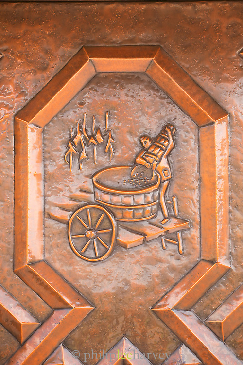 Close-up of copper plaque showing the process of wine making, Wiltingen, Germany