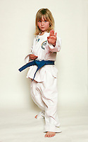 7 February 2008: 7 year old Caitlyn Nickerson Tae Kwon Do athlete in motion wearing a blue belt. Young kids practicing Taekwondo at the USA Black Belt Academy in Huntington  Beach, CA. Tae Kwon Do is a Korean Martial Art discipline that trains the body and mind.  It is global sport that is an official Olympic sport.