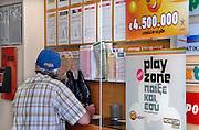 Griekenland, Thessaloniki, 11-6-2011Straatbeeld van deze stad in Noord Griekenland. In een gokkantoor vult een man een totoformulier in. Het is de tweede stad van het land.Griekenland is zwaar getroffen door het wanbeleid van voorgaande regeringen op financieel gebied. Foto: Flip Franssen
