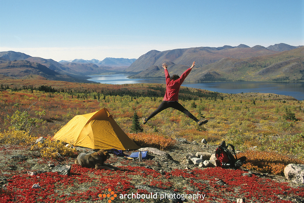 A woman jumps for joy while camping in the Yukon.